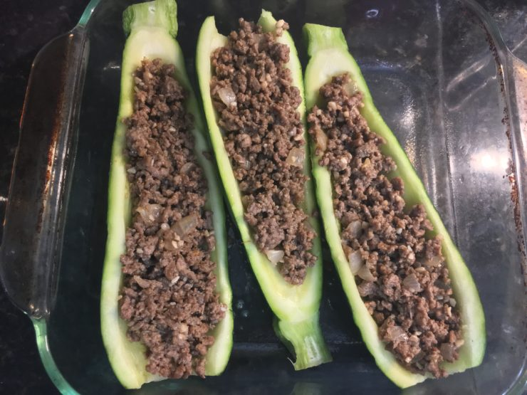 A casserole dish with three scooped out zucchinis in the dish filled with taco meat.