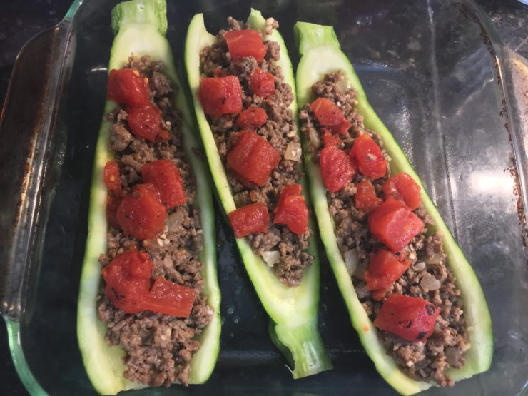 A casserole dish with three scooped out zucchinis in the dish filled with taco meat and diced, fire roasted tomatoes.