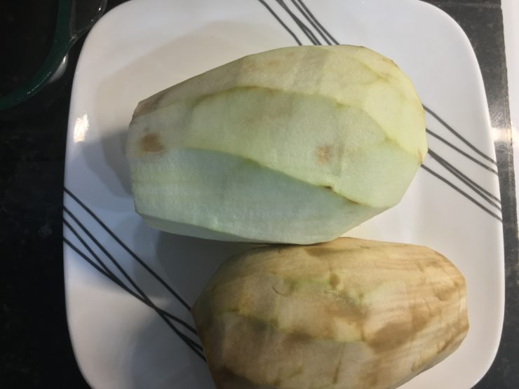 A white plate with black stripes and two very large, peeled, eggplants on the plate.