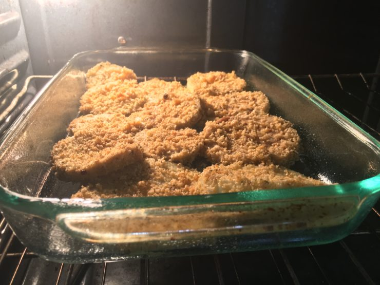 A glass 9x13 casserole dish with eggplants sliced into rounds that have been dipped in beaten egg and rolled in Panko Italian Breadcrumbs, lined up in the casserole dish. The casserole dish has been placed into the oven.