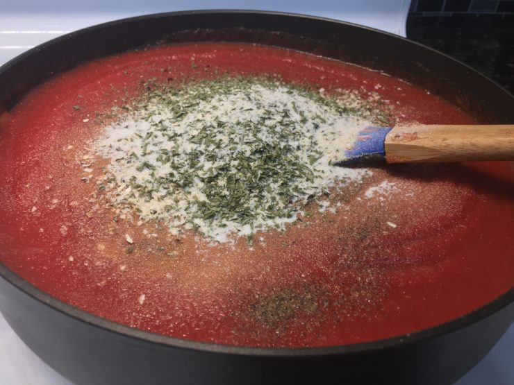 A large black skillet on a white stove with tomato sauce and crushed tomatoes inside the skillet and a wooden handled, blue spatula in the sauce. Garlic powder, minced onion, onion powder, dried basil flakes, dried parsley flakes, salt, pepper, and garlic salt have been added to the top of the sauce but haven't been stirred in yet.