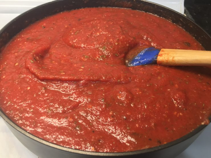 A large black skillet on a white stove with tomato sauce and crushed tomatoes inside the skillet and a wooden handled, blue spatula in the sauce. Garlic powder, minced onion, onion powder, dried basil flakes, dried parsley flakes, salt, pepper, and garlic salt have been added to the top of the sauce and stirred in along with fire roasted diced tomatoes.