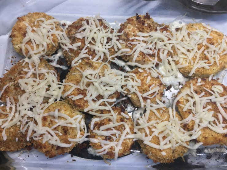 A glass 9x13 casserole dish with eggplants sliced into rounds that have been dipped in beaten egg and rolled in Panko Italian Breadcrumbs, lined up in the casserole dish. The eggplant has been baked and is topped with shredded mozzarella cheese.