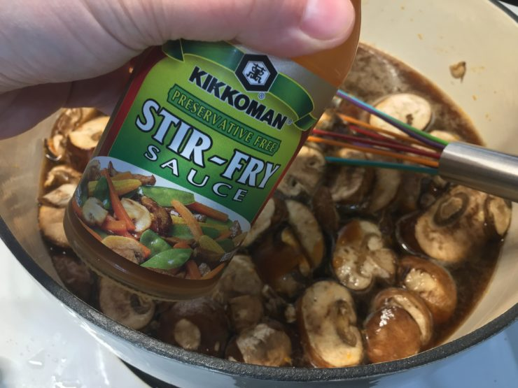 A white dutch oven with broth, seasonings, and baby portabella mushrooms inside and bottle of Kikkoman Stir Fry Sauce being held over the Dutch oven.