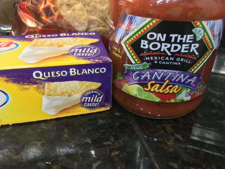A box of Queso Blanco Velveeta cheese dip along with a jar of On The Border mild Cantina salsa with a bag of white corn tortilla chips behind it all.