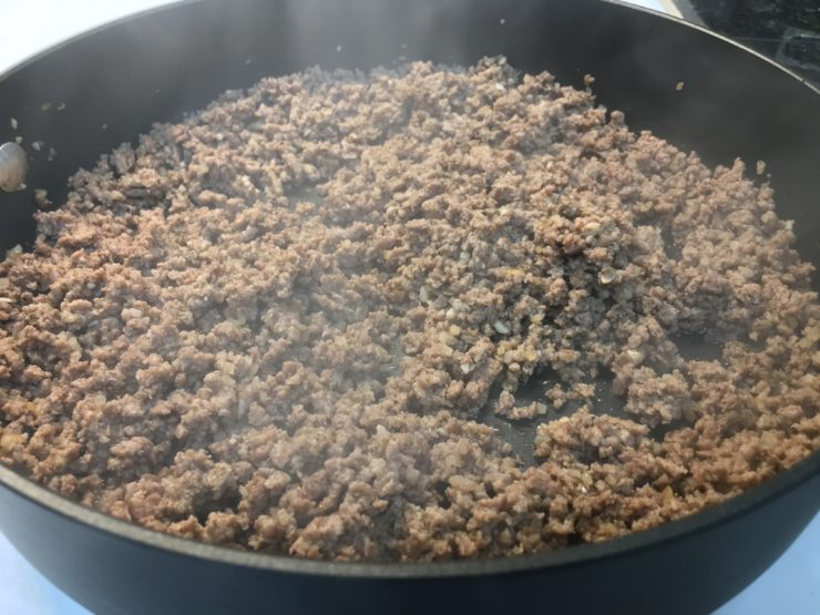 A large, deep, black skillet with cooked and crumbled lean ground beef with taco seasoning inside.