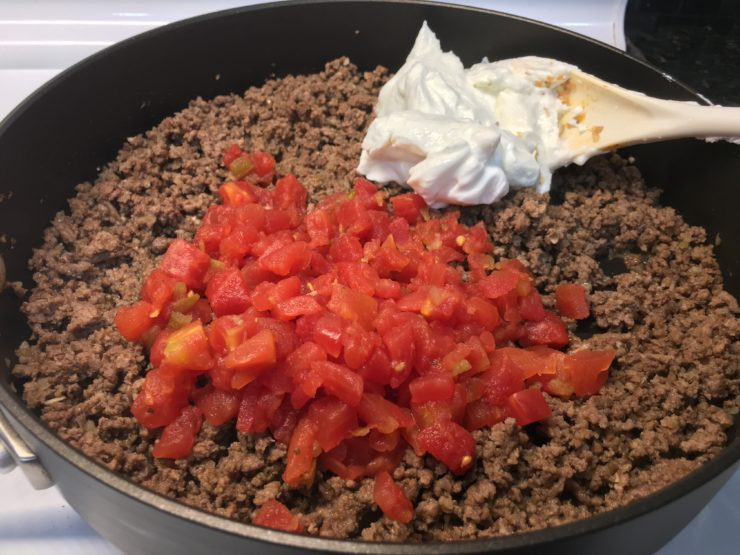 A large, deep, black skillet with cooked and crumbled lean ground beef with taco seasoning inside. One, 10.5 ounce can of mild diced tomatoes with green chilies has been drained and added to the skillet of cooked ground beef along with 1/2 cup of plain, nonfat Greek yogurt. A white spoon is in the skillet to stir the contents together.