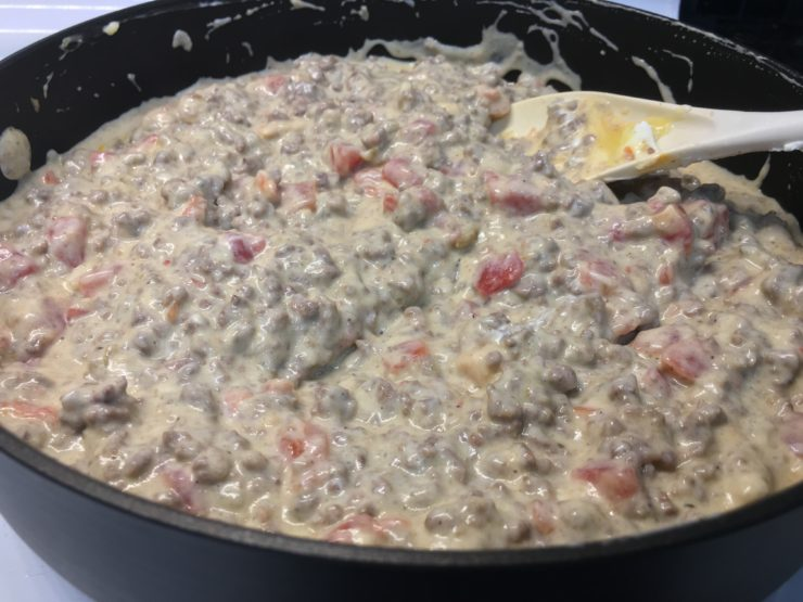 A large, deep, black skillet with cooked ground beef inside with tomatoes with green chilies, plain nonfat Greek yogurt, and healthy condensed cream of chicken soup. Everything has been stirred together with a white spoon and all ingredients are well blended and mixed.