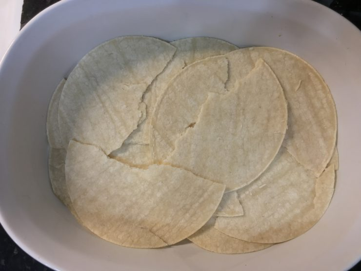 A 8x12 white casserole dish that has been sprayed with nonstick cooking spray and has torn white corn tortillas layering the bottom of the dish.