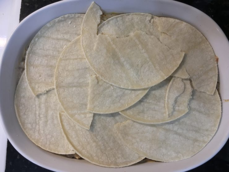 The final layer of torn corn tortillas has been added to the top of the Beef Enchilada Casserole in the white casserole dish.
