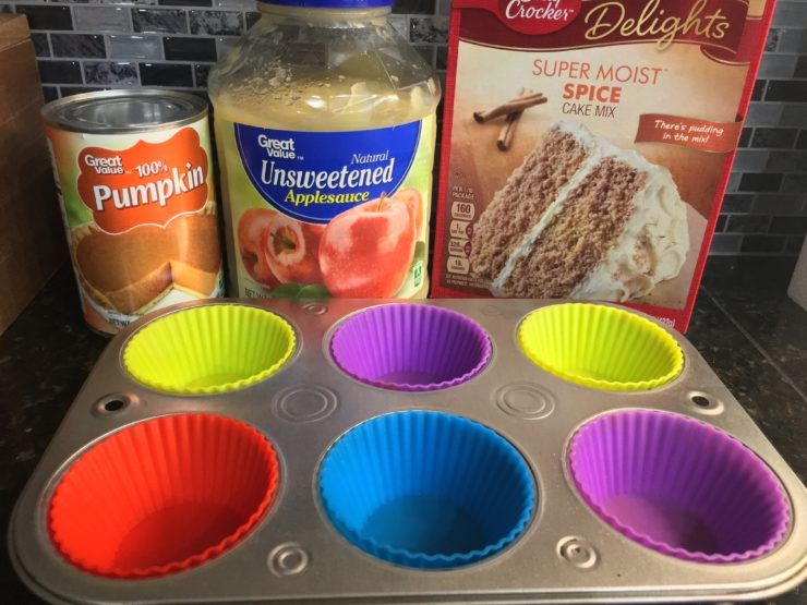 A regular sized can of pumpkin puree, a jar of unsweetened applesauce, a box of Betty Crocker Super Moist Spice Cake Mix, and a half dozen silver muffin tin with six multicolored silicone muffin liners in the tin.