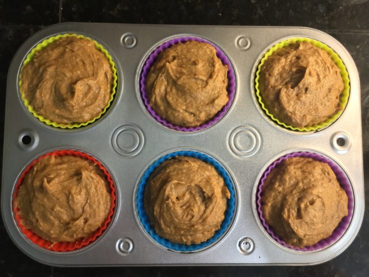 A silver, half dozen muffin tin with six silicone muffin liners filled with Three Ingredient Pumpkin Muffins in the pan.