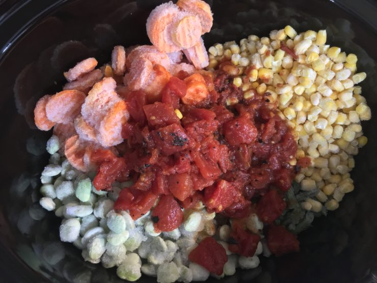 A six quart black slow cooker Crock Pot with frozen sliced carrots, frozen lima beans, frozen green peas, frozen green beans, and frozen whole kernel corn in the slow cooker. A can of fire roasted tomatoes has been added to the ingredients in the slow cooker.