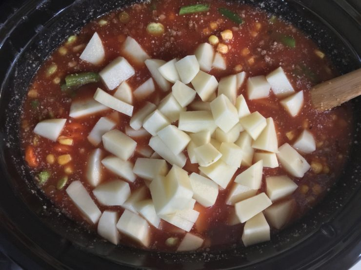 A six quart black slow cooker Crock Pot with frozen sliced carrots, frozen lima beans, frozen green peas, frozen green beans, and frozen whole kernel corn in the slow cooker. A can of fire roasted tomatoes has been added to the ingredients in the slow cooker. Chicken broth and tomato sauce has also been added to the ingredients in the slow cooker. The cooked, ground beef and peeled, diced, russet potatoes have also been added to the ingredients in the slow cooker.