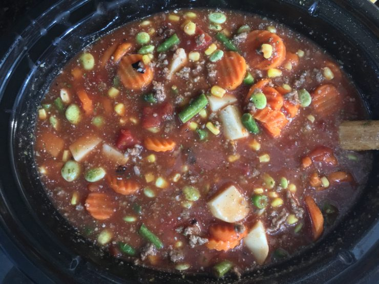 A six quart black slow cooker Crock Pot with frozen sliced carrots, frozen lima beans, frozen green peas, frozen green beans, and frozen whole kernel corn in the slow cooker. A can of fire roasted tomatoes has been added to the ingredients in the slow cooker. Chicken broth and tomato sauce has also been added to the ingredients in the slow cooker. The cooked, ground beef and peeled, diced, russet potatoes have also been added to the ingredients in the slow cooker. Dried basil flakes, dried parsley flakes, salt, pepper, onion powder, garlic powder, Lawry's seasoned salt, and Tony's Creole Seasoning has been added to the ingredients in the slow cooker. All ingredients have been stirred together with a wooden spatula.