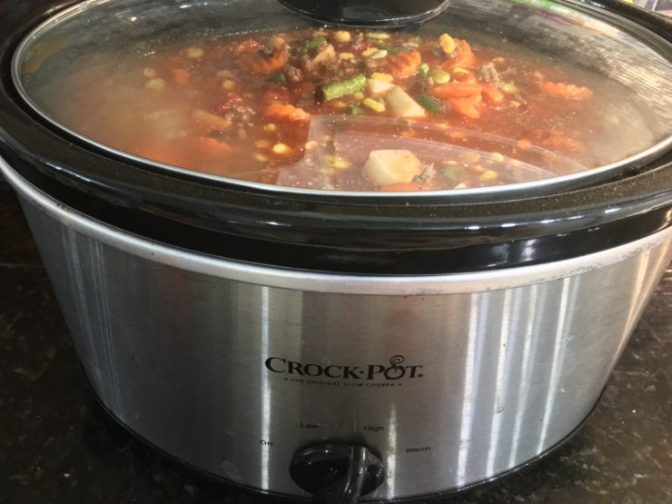 A six quart black slow cooker Crock Pot with frozen sliced carrots, frozen lima beans, frozen green peas, frozen green beans, and frozen whole kernel corn in the slow cooker. A can of fire roasted tomatoes has been added to the ingredients in the slow cooker. Chicken broth and tomato sauce has also been added to the ingredients in the slow cooker. The cooked, ground beef and peeled, diced, russet potatoes have also been added to the ingredients in the slow cooker. Dried basil flakes, dried parsley flakes, salt, pepper, onion powder, garlic powder, Lawry's seasoned salt, and Tony's Creole Seasoning has been added to the ingredients in the slow cooker. All ingredients have been stirred together with a wooden spatula. A lid has been placed on the crockpot and it is set to cook on high.