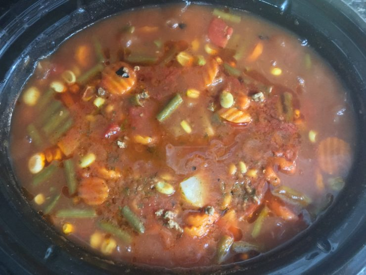 A six quart Crock Pot slow cooker with cooked Vegetable Beef Soup inside.