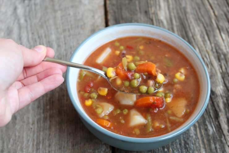 A gray and white bowl with Slow Cooker Vegetable Beef Soup inside. A hand is holding a silver spoon with the soup on it out of the bowl. The bowl is sitting on a wood back drop.