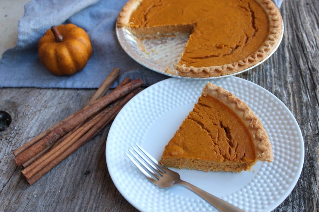 The photo is of a pumpkin pie in a silver pie pan, missing one slice. The pumpkin pie is a deep, pumpkin orange with a golden brown crust. The missing slice of pie is on a white, hobnail dessert plate with a silver fork placed on the front, right hand corner of the plate. A blue towel is placed under the pie pan and an artificial, small orange pumpkin is sitting on the left hand side of the pie, toward the front and edge of the blue towel. A bunch of cinnamon sticks are casually placed in a bundle directly in front of the pie pan and to the front left of the white dessert plate. Everything is sitting on a weathered barn wood back drop.