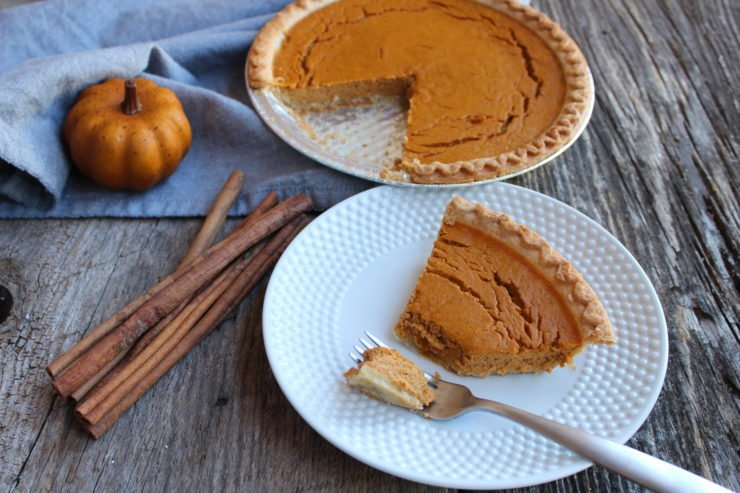 The photo is of a pumpkin pie in a silver pie pan, missing one slice. The pumpkin pie is a deep, pumpkin orange with a golden brown crust. The missing slice of pie is on a white, hobnail dessert plate with a silver fork placed on the front, right hand corner of the plate. The silver fork has a bite of the pumpkin pie on it, and the slice of pumpkin pie on the white plate is missing a bite. A blue towel is placed under the pie pan and an artificial, small orange pumpkin is sitting on the left hand side of the pie, toward the front and edge of the blue towel. A bunch of cinnamon sticks are casually placed in a bundle directly in front of the pie pan and to the front left of the white dessert plate. Everything is sitting on a weathered barn wood back drop.
