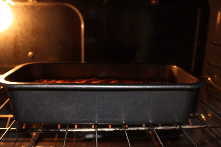 A gray, standard sized loaf pan filled with Easy Pumpkin Bread batter is placed in a hot oven.