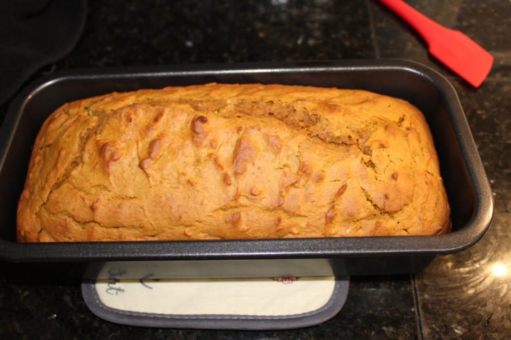 A gray, standard sized loaf pan with baked Easy Pumpkin Bread inside sitting on a black, granite counter top.
