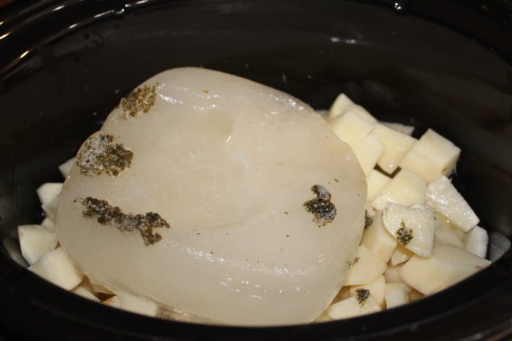 A black slow cooker with peeled and diced russet potatoes inside along with chicken broth, part of which is still frozen in a block.
