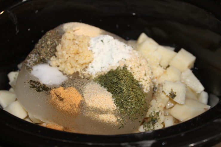 A black slow cooker with peeled and diced russet potatoes inside along with chicken broth, part of which is still frozen in a block. Salt, Seasoned Salt, ground black pepper, dried basil flakes, dried parsley flakes, onion powder, Ranch seasoning, fresh minced garlic, and dried minced onion has been added to the Crock Pot slow cooker.
