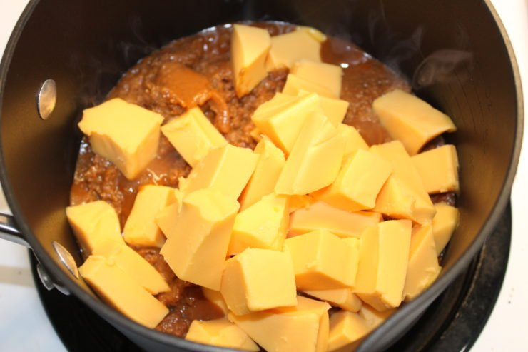 A black pot with fifteen ounces of Armor, no bean chili inside. Sixteen ounces of cubed Velveeta Cheese has been added to the chili in the pot.