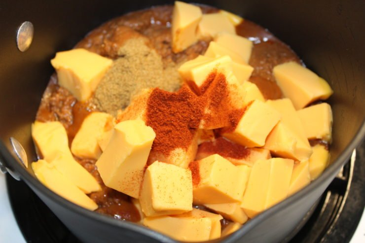 A black pot with no bean chili, sixteen ounces of cubed Velveeta Cheese, paprika, and cumin.
