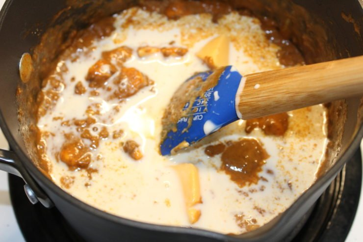 A black pot with no bean chili, sixteen ounces of cubed Velveeta Cheese, paprika, and cumin along with one fourth of a cup of evaporated milk. A blue, wooden handled spatula is resting in the pot.