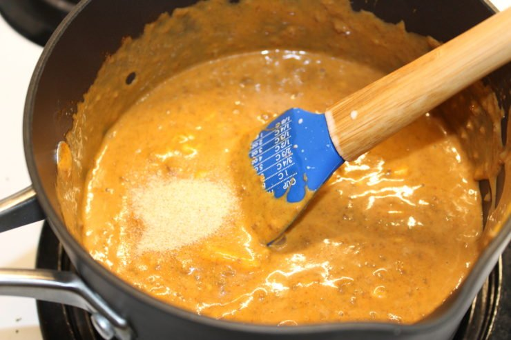 A black pot with no bean chili, sixteen ounces of cubed Velveeta Cheese, paprika, and cumin along with one fourth of a cup of evaporated milk. All ingredients have been stirred together and garlic powder has been added in. A blue, wooden handled spatula is resting in the pot.