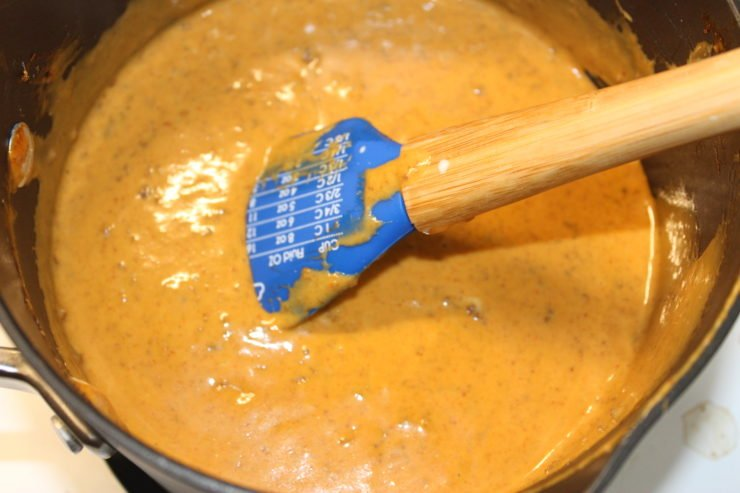 A black pot with no bean chili, sixteen ounces of cubed Velveeta Cheese, paprika, and cumin along with one fourth of a cup of evaporated milk and garlic powder. All ingredients have been stirred together and a blue wooden handled spatula is resting in the pot.