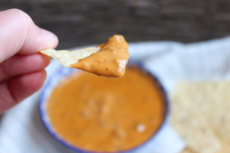 A blue and white flower printed bowl with Chili's Queso Dip Recipe inside. A white and gray striped towel is under the bowl with white corn chips to the right of the bowl on the towel. Everything sits on a wooden board backdrop. A hand is holding a tortilla chip that has been dipped in the Chili's Queso Dip Recipe and that is the focus of the frame.