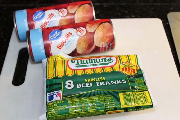 Two cans of red and blue packaged Great Value Buttermilk Biscuits are sitting on a white cutting board with a yellow and green package of eight Nathan's Famous Skinless Beef Franks. The cutting board is sitting on a black granite counter top.