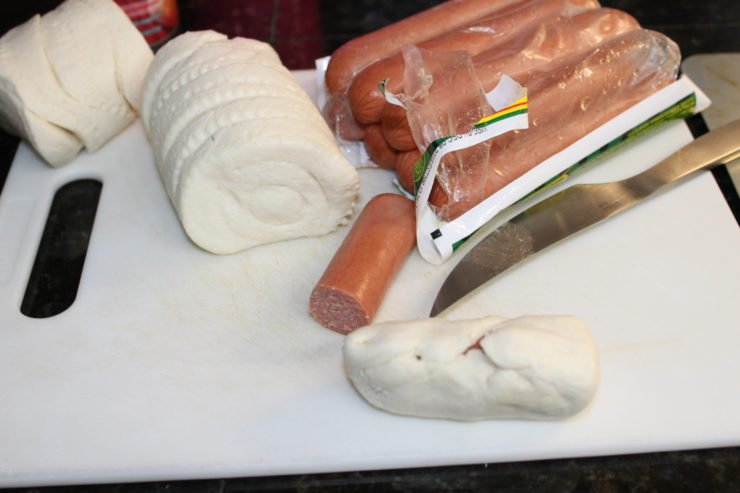 Round, white, biscuit dough, straight out of the can are lined up on the left side of a white cutting board, making eleven individual small biscuits. The package of Nathan's skinless beef franks has been turned over and is cut open and is in the upper right corner of the cutting board. The hot dogs are visible in the package and one hot dog has been sliced in half and is laying on the front of the cutting board. One half of the hot dog is laying in the center of a flattened out biscuit dough and the dough has been wrapped around the hot dog until you can't see the hot dog anymore. A silver paring knife is laying on the cutting board on the right hand side and the cutting board is on a black, granite counter top.