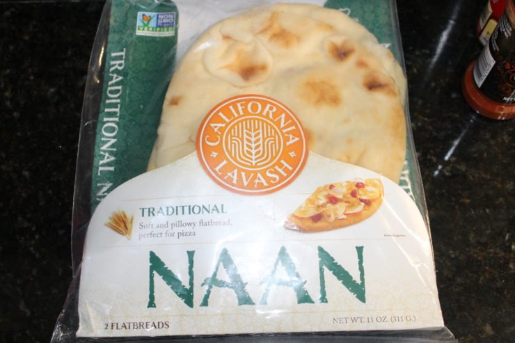 An unopened package of California Lavash Naan bread sitting on a black granite counter top.