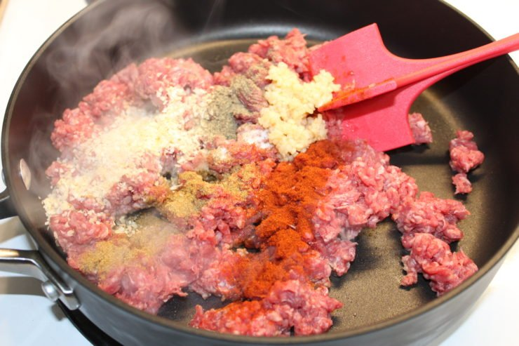 A large black skillet with one pound of uncooked ground beef inside. The ground beef has seasonings on top and the seasonings are dried minced onion, cumin, fresh minced garlic, paprika, salt, and ground black pepper. A red meat muddler is inside the skillet and the meat is slightly broken up. Steam is coming off of the meat because the skillet is on and cooking the meat.
