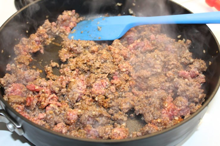 A large black skillet with one pound of partially cooked lean ground beef inside that has been seasoned with homemade taco seasoning. A blue spatula is in the skillet stirring the meat around and steam is coming off the meat as it is being cooked on a white stove.