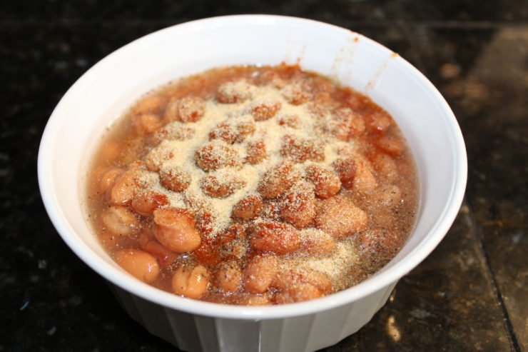 A small white bowl that is filled with pinto beans that have been seasoned with garlic powder, ground black pepper, salt, and paprika. The bowl is sitting on a black granite counter top.