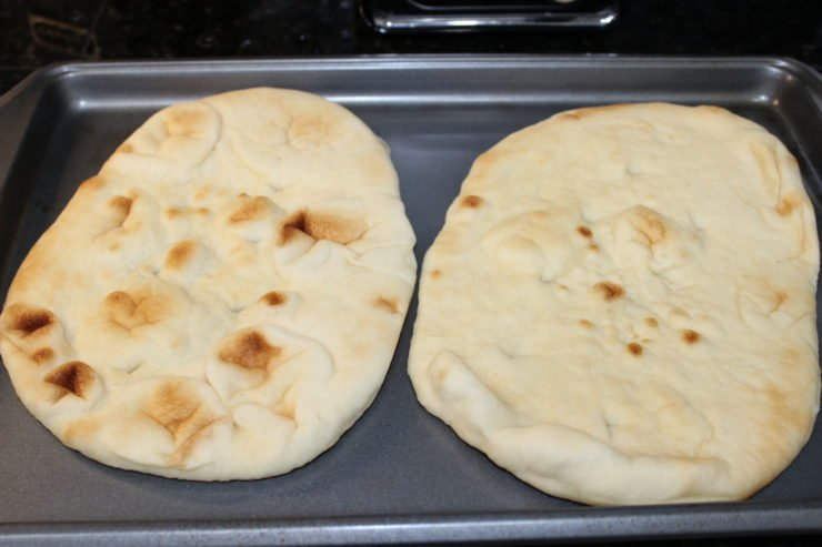 A silver sheet pan with two slices of California Lavash Naan bread on the sheet pan. The pan is sitting on a black granite counter top with a silver toaster visible just in the background.