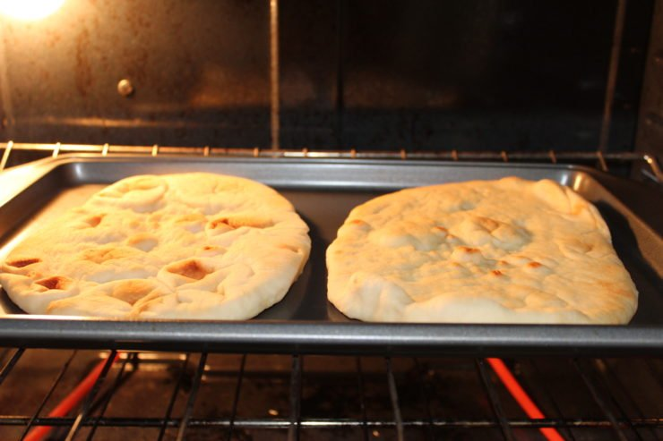 A silver sheet pan with two slices of California Lavash Naan bread on the pan. The pan has been placed in the oven and the oven is on.