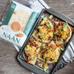 A silver sheet pan with California Lavash Naan bread that is topped with pinto beans, ground beef taco meat, shredded American and Colby cheese, shredded lettuce, and diced tomatoes. A white and black Aztec design towel is under the sheet pan. There are four Indian Tacos on the sheet pan and everything is sitting on a wooden backdrop. A package of California Lavash Naan bread is placed in the upper left corner beside the pan of tacos.