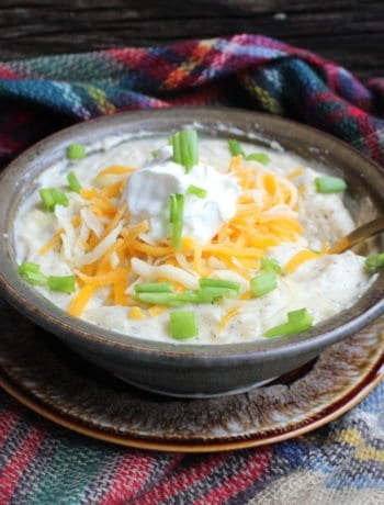 A green and brown clay soup bowl with a brown plate underneath and a golden spoon is in the soup, on the right hand side of the soup bowl. The soup bowl is filled with Crockpot Loaded Potato Soup, topped with sour cream, shredded American and Colby cheese, and freshly cut chives. A red, blue, green, yellow, and tan plaid scarf is wrapped around the soup bowl and under it and everything is placed on a wooden board backdrop.