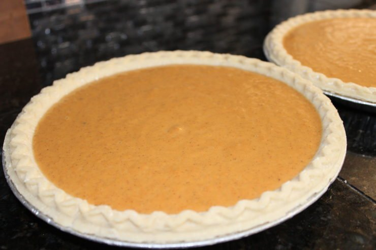 In the forefront is a uncooked Pumpkin Pie in an unbaked pie crust that is in a silver, foil, pie pan. In the background is a second unbaked pumpkin pie, identical to the first. Both pies are sitting on a black, granite counter top.
