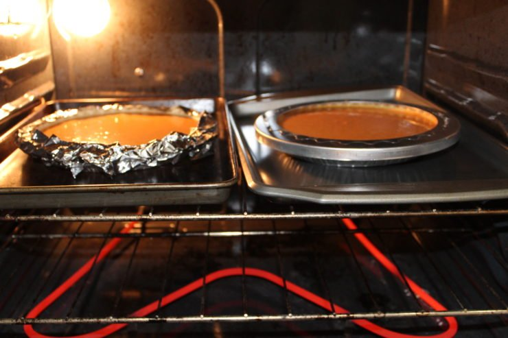 An open oven, with the oven and light on. Two silver sheet pans are in the oven with two uncooked pumpkin pies on the sheet pans. One pumpkin pie is covered with a pie crust saver and the other has strips of foil folded over the edges of the crust.