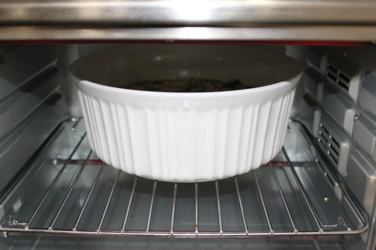 This photo is of a round, white casserole dish full of uncooked Easy Breakfast Casserole that has been placed inside a silver, convection oven. The oven is on and the photo is taken with the oven door open, looking into the oven.