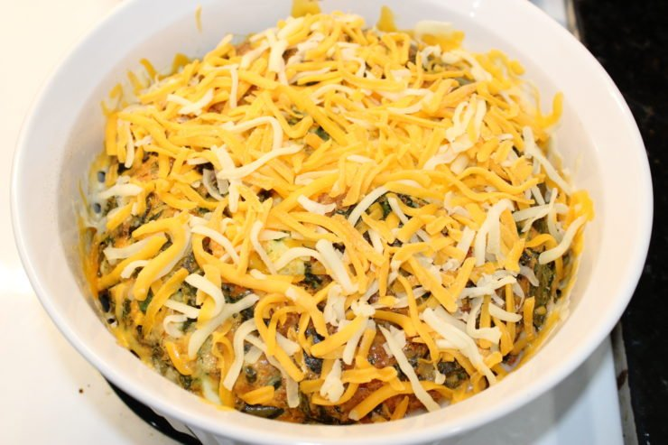 A large, white, round casserole dish full of baked Easy Breakfast Casserole is sitting on a white stove top. The casserole has been top with uncooked, shredded American and Colby cheese blend and is about to be placed back in the oven for the cheese to melt.