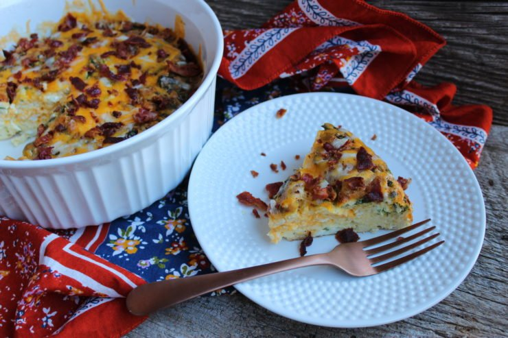 This photo is of a round, white, casserole dish, filled with Easy Breakfast Casserole that has been topped with gooey melted cheese and crispy bacon bits. A orange, blue, and purple floral colored towel has been haphazardly arranged underneath the casserole dish and everything is sitting on a weather wood backdrop. A slice of the Easy Breakfast casserole is missing and has been placed to the right hand side of the white casserole dish on a white hobnailed plate. The slice of breakfast casserole is topped with melted cheese and crispy bacon bits with some bacon bits scattered on the plate that have fallen from the top of the slice of casserole. A bronze fork has been placed to the right hand side of the plate.