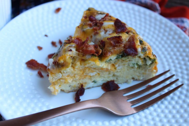 A close up of a white, hobnail late with a triangular slice of Easy Breakfast Casserole in the middle of the plate is in full frame in this photo. A bronze fork is placed on the right hand side of the plate and the slice of Breakfast Casserole is topped with melted cheese and crispy bacon bits. Some of the bacon bits have fallen off onto the plate and a multi colored floral towel has been placed underneath the plate, just barely visible.
